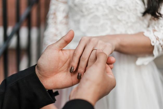 Bruidegom die trouwring op de vinger van de bruid plaatst