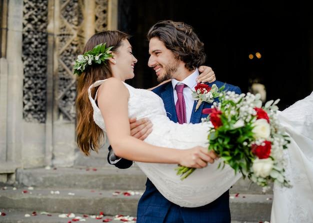 Bruidegom die zijn mooie bruid opheft