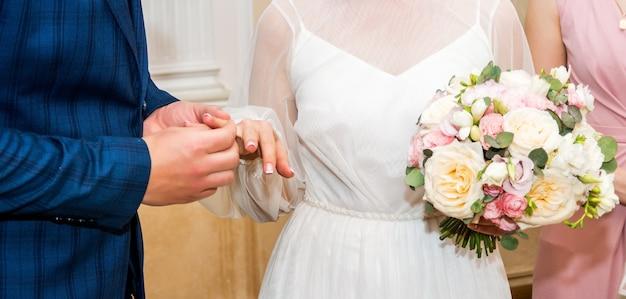 Bruidegom draagt bruid een trouwring bruidshand houdt een mooi bruidsboeket vast ...