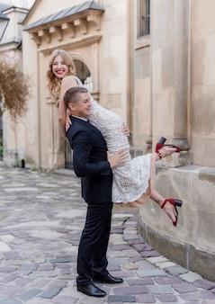Bruidegom draagt de bruid op de schouder, gelukkige paar, trouwdag, buitenshuis