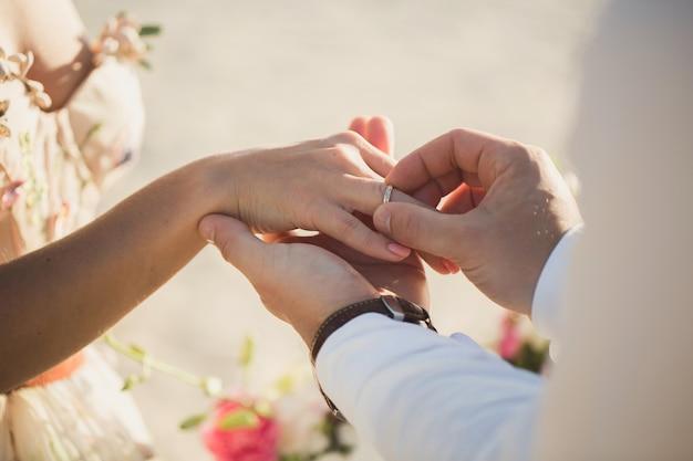 Bruidegom draagt ring aan de vinger van de bruid