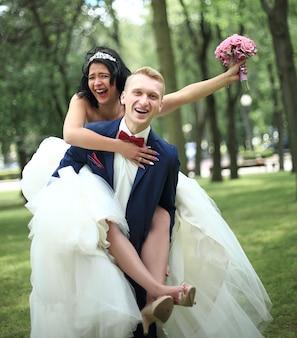 Bruidegom draagt zijn bruid op de rug in het park. buitenshuis