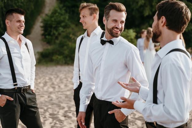 Bruidegom en beste mannen poseren op het strand
