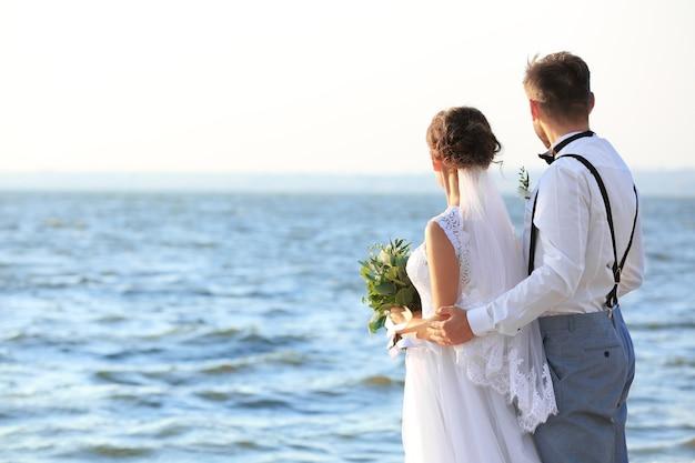 Bruidegom en bruid aan de oever van de rivier