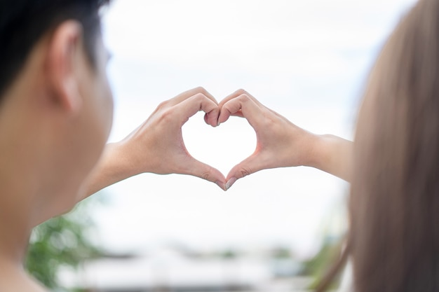 Bruidegom en bruid coördineren hun hand samen om een hartvorm te creëren met de heldere hemel