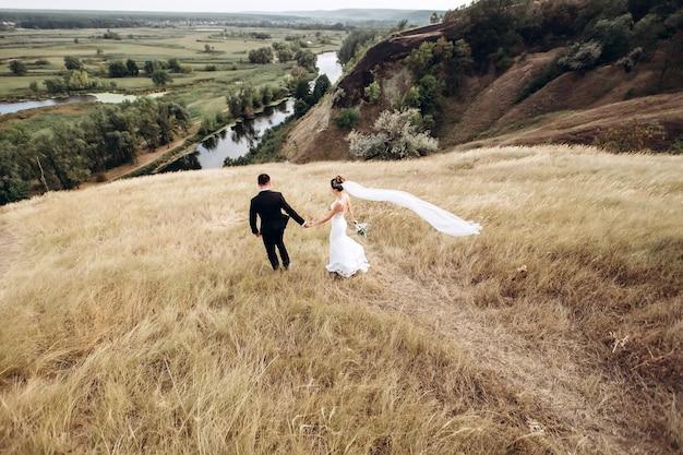 Bruidegom en bruid die buiten stellen