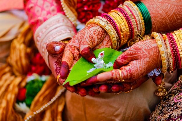 Bruidegom en bruid die groen blad en het beeldhouwwerk van lord ganesha in de hand houden