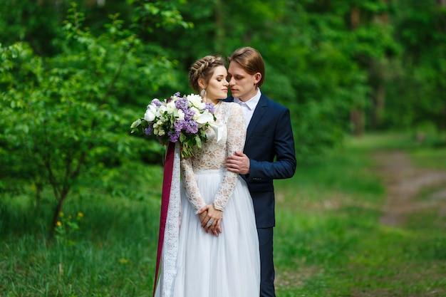 Bruidegom en bruid die huwelijksboeket met lila bloemen op vegetatieachtergrond houden
