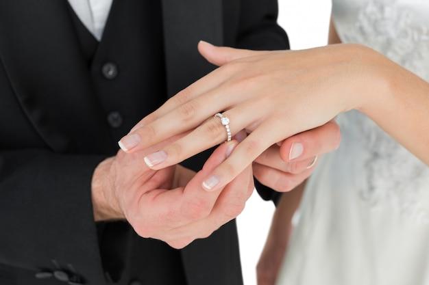 Bruidegom en bruid die trouwring ruilen