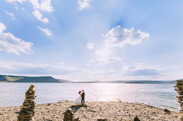 Bruidegom en bruid die van warme dag op een meer op de winderige dag genieten
