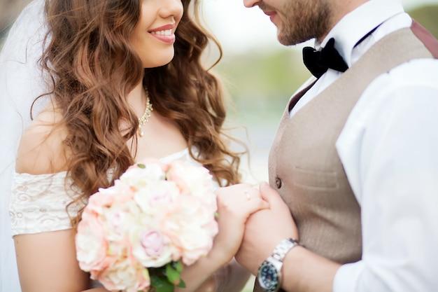 Bruidegom en bruid houden boeket van kleine rozen
