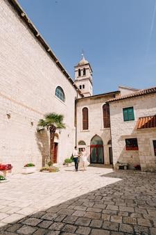 Bruidegom en bruid in een witte kanten jurk lopen langs de binnenplaats van een oud gebouw langs badkuipen met