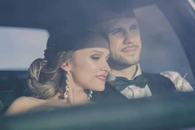 Bruidegom en bruid in retro auto