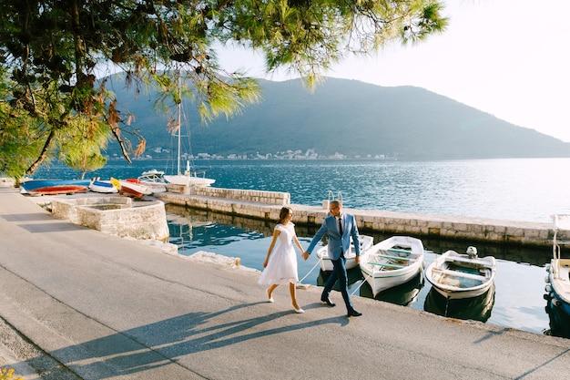 Bruidegom en bruid lopen hand in hand langs de zeekust tegen de achtergrond van jachten op een zonnige dag