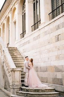 Bruidegom en bruid omarmen staan op de trappen van een oud gebouw in bergamo, italië