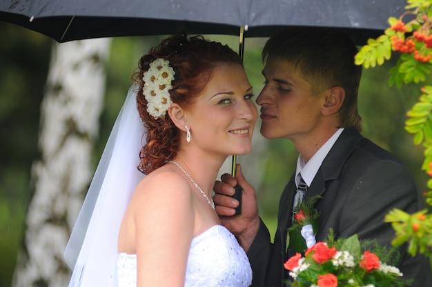 Bruidegom en bruid portret, kussen in de regen