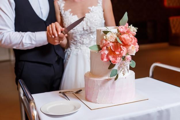 Bruidegom en bruid snijden prachtige bruidstaart op meerdere niveaus, versierd met crèmerode bloemengroen green