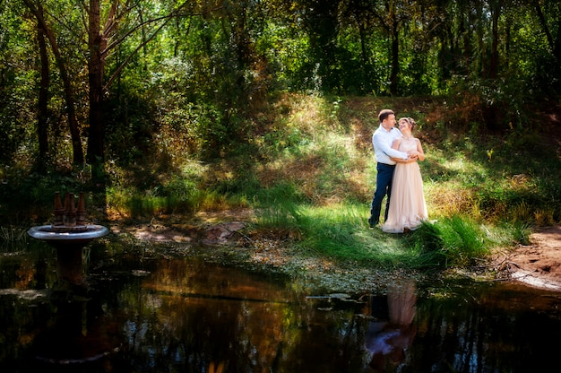 Bruidegom en bruid staan aan de waterkant omringd door prachtig groen