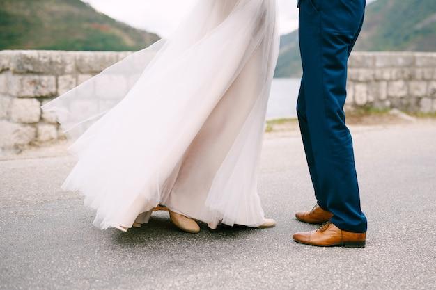Bruidegom en bruid staan tegen de stenen muur
