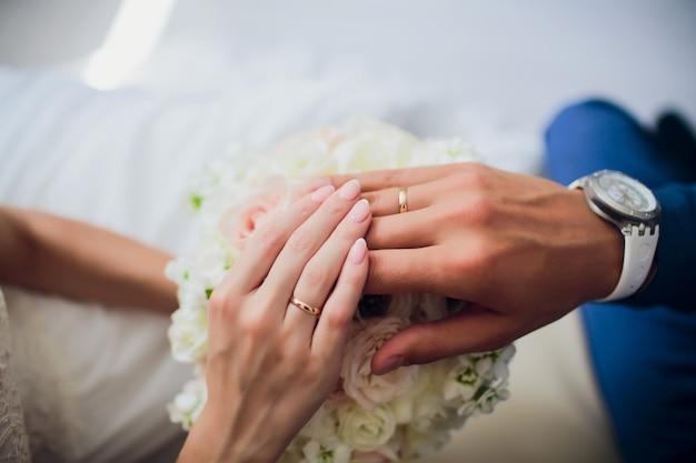 Bruidegom en bruidenhanden met ringen, close-upmening.