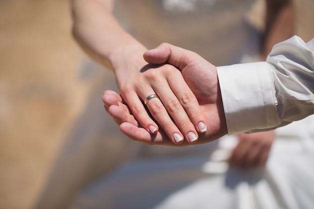 Bruidegom en bruidenhanden met ringen, close-upmening