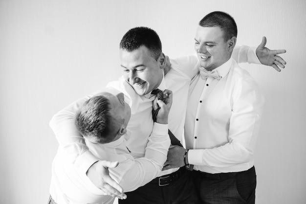 Bruidegom en bruidsjonkers hebben plezier, zwart en wit