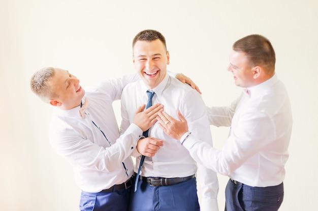 Bruidegom en bruidsjonkers in stijlvolle witte overhemden en blauwe broeken. vrienden hebben plezier.