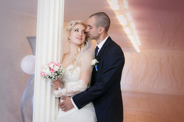 Bruidegom en de bruid met een bruiloft boeket staan in de buurt van een witte kolom
