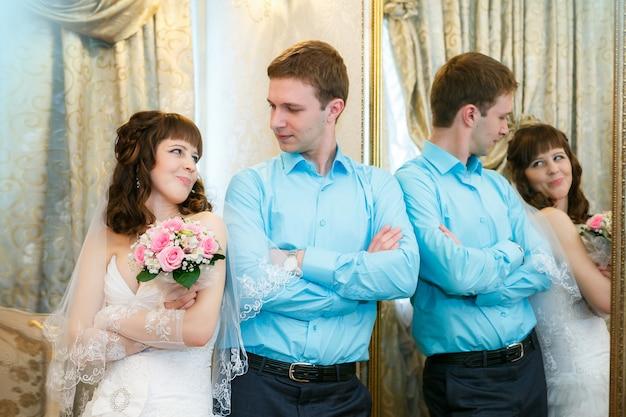 Bruidegom en de bruid staan in de buurt van een spiegel met een gouden frame
