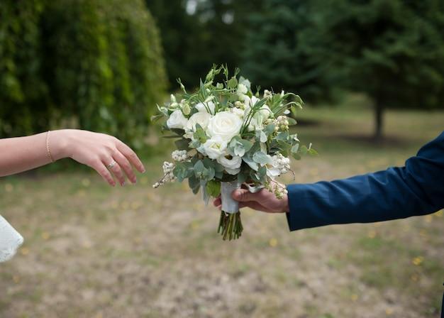 Bruidegom geeft de bruid een mooi bruidsboeket