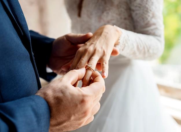 Bruidegom gezet op trouwring bruid hand