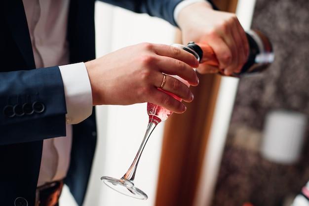 Bruidegom giet rode champagne uit een fles in een glas