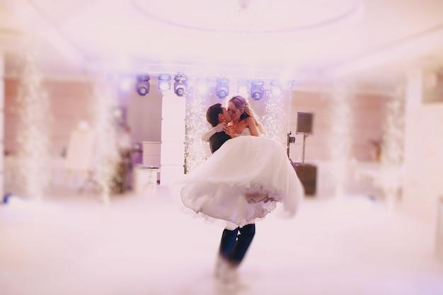 Bruidegom het opheffen van de bruid tijdens het dansen