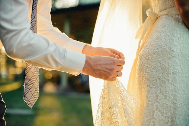 Bruidegom houden bruid de jurk in handen op hun trouwdag