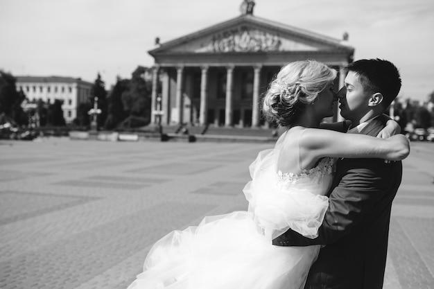 Bruidegom houdt bruid in zijn armen en verdraaid