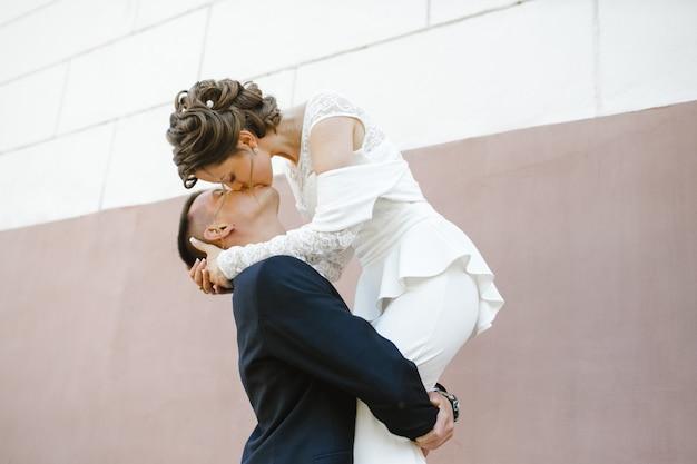 Bruidegom houdt bruid op zijn handen en kust haar