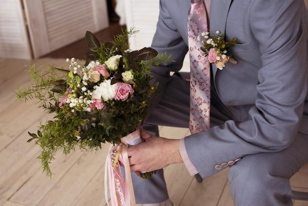 Bruidegom houdt bruids boeket op de bruiloft