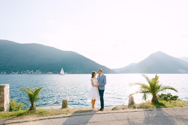 Bruidegom houdt de handen van de bruid vast aan de kust tegen de bergen
