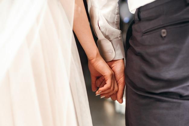 Bruidegom houdt de vingers van de bruid zacht in zijn arm