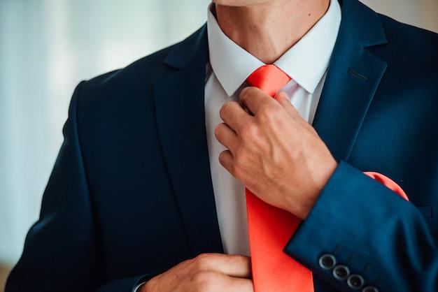 Bruidegom houdt handen op de stropdas, trouwpak