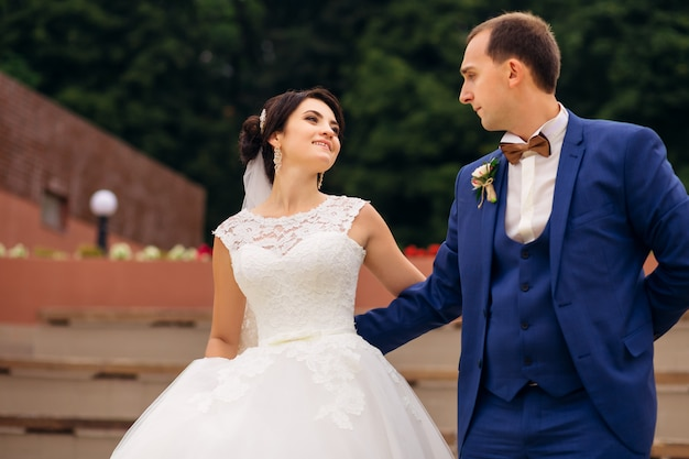 Bruidegom in blauw pak en bruid in trouwjurk kijken elkaar