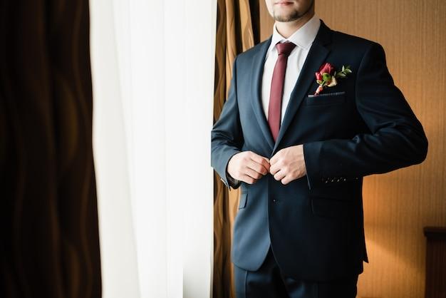 Bruidegom in een blauwe jas een man knoopt zijn jas dicht de bruidegoms vergoedingen