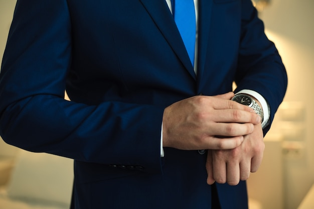 Bruidegom in een jas een man in een blauwe jas trouwdag bruidegomsvergoeding de man let op de tijd