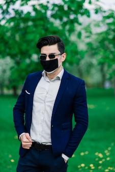 Bruidegom in een medisch masker vóór de huwelijksceremonie in het park buiten. bruiloften tijdens de periode van quarantaine en pandemie van coronavirusinfectie