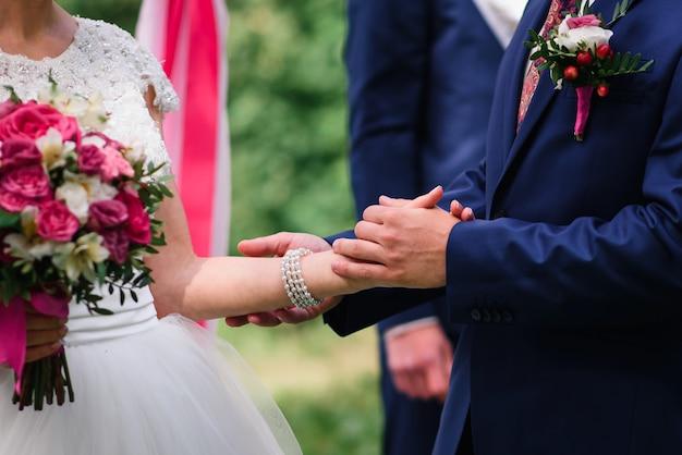 Bruidegom in een pak houdt de hand van de bruid in een witte jurk op de bruiloft