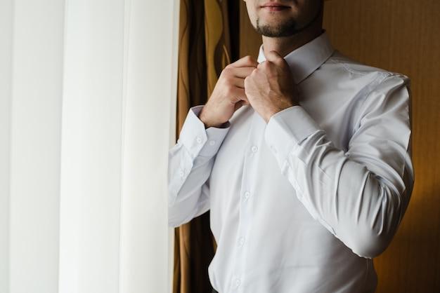 Bruidegom in een wit overhemd een man knoopt zijn overhemd dicht de bruidegoms vergoedingen