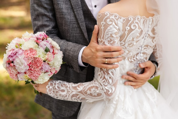 Bruidegom in grijs pak omarmen bruid in trouwjurk met lange mouwen
