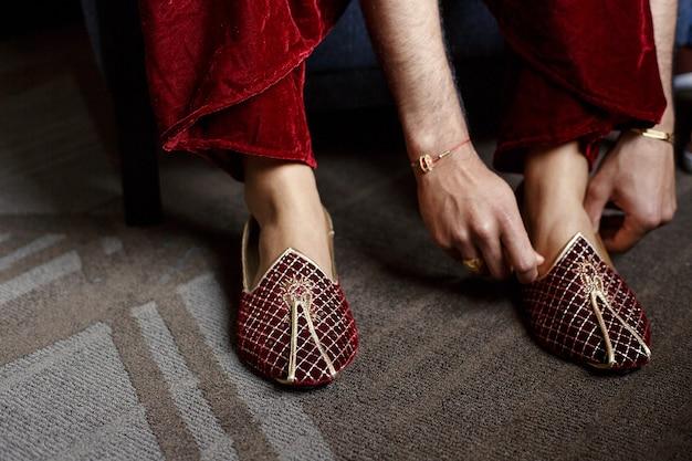 Bruidegom in rood fluwelen broek zet op gouden trouwschoenen