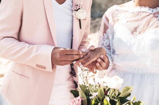 Bruidegom in roze jas draagt ring aan de vinger van de bruid op het strand