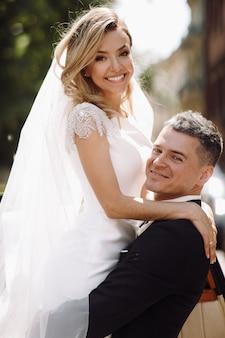 Bruidegom in zwarte smoking hugs tedere prachtige bruid terwijl ze stan